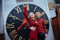 Portrait of beautiful stylish couple standing near the clock. A Royalty Free Stock Photo