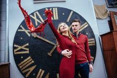 Portrait of beautiful stylish couple standing near the clock. A Stock Photo