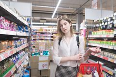 Portrait of a beautiful stylish girl on the background of shelves with products in a supermarket royalty free stock photography
