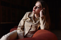 Portrait of beautiful stylish young lady in suit sitting on the red sofa Stock Photos