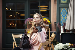 Portrait of beautiful stylish young woman sitting in street cafe . Model looking aside. City lifestyle. Female fashion Stock Photos