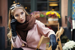 Portrait of beautiful stylish young woman sitting in street cafe . Model looking aside. City lifestyle. Female fashion Royalty Free Stock Photos