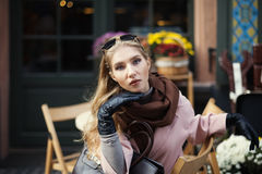 Portrait of beautiful stylish young woman sitting in street cafe . Model looking at camera. Close up. City lifestyle Royalty Free Stock Image