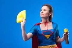 Portrait of beautiful superwoman with rag and detergent for cleaning. Isolated on blue royalty free stock photography