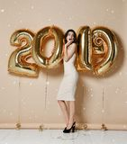 Portrait Of Beautiful surprised Girl In Shiny Golden Dress Throwing Confetti, Having Fun With Gold 2018 Balloons On Background. royalty free stock images