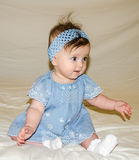 Portrait of the beautiful sweet little baby girl in a blue dress with a hairpin on the head that smiles Stock Photo