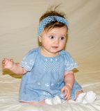 Portrait of the beautiful sweet little baby girl in a blue dress with a hairpin on the head that smiles. Portrait of the beautiful sweet little baby girl in a Stock Image