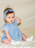 Portrait of the beautiful sweet little baby girl in a blue dress with a hairpin on the head that smiles. Portrait of the beautiful sweet little baby girl in a Royalty Free Stock Photo