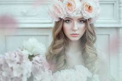 Portrait of a beautiful, sweet woman with roses in curly hair. Around flowers. Stock Photos