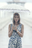 Portrait of beautiful tan skin woman with umbrella standing amon Stock Image