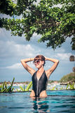 Portrait of beautiful tanned woman in black swimwear relaxing in swimming pool spa. Hot summer day and bright sunny Royalty Free Stock Images