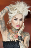 Portrait of beautiful tattooed woman with hand in hair Royalty Free Stock Image