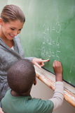 Portrait of a beautiful teacher and a pupil making an addition Stock Photo