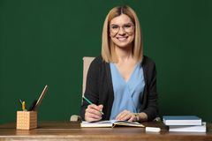 Portrait of beautiful teacher sitting at table stock photography