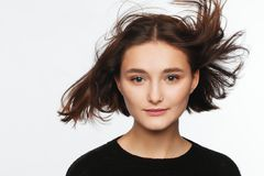 Portrait of a beautiful teen girl in a black sweater on a white background royalty free stock photography