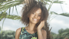 Portrait of beautiful teenage Afro American girl on tropical beach smiling to a camera. Stock Image