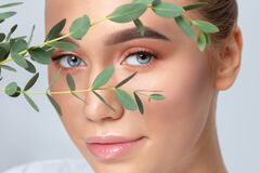 Portrait of a beautiful teenage girl with beautiful makeup and healthy clean skin. Near the face is a branch of eucalyptus. Makeup