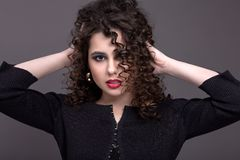 Portrait of a beautiful teenage girl with a bright make-up on a. Gray background. With curly hair and red lipstick Royalty Free Stock Photo