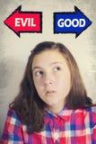 Portrait of beautiful teenage girl choosing between GOOD and EVI Stock Photos