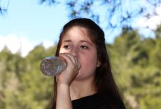 A beautiful teenage girl drinking water royalty free stock images