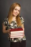 Portrait of  beautiful teenage girl holding many books Royalty Free Stock Images
