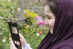 Portrait of a Beautiful Teenage Girl Outdoor in A Garden Enjoyin. G and  Playing with Smart Phone Royalty Free Stock Image