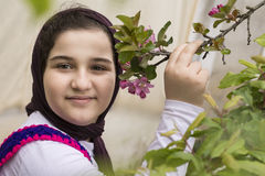 Portrait of a Beautiful Teenage Girl Outdoor in A Garden. Touching Apple Tree Stem with Fresh Buds Viewing Directly to the Camera Stock Photo