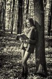 Portrait of a beautiful teenage girl reading a book in the fores Royalty Free Stock Image