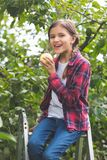 Toned portrait of beautiful teenage girl sitting on stepladder at orchard and eating fresh apple Royalty Free Stock Photos