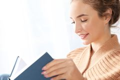 Portrait of beautiful teenage girl in warm cozy sweater reading book near window royalty free stock photos