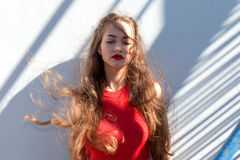 Portrait of a beautiful teenage girl in a youth style. Portrait of a beautiful teen girl in a youth style standing by the wall. In the red top Royalty Free Stock Photos