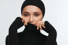 Portrait of a beautiful teenager girl in a black golf sweater and hat stock images