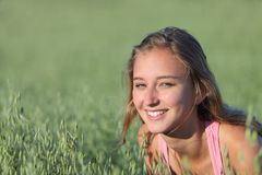 Portrait of a beautiful teenager girl smiling in a meadow. Portrait of a beautiful teenager girl smiling in an unfocused green oat meadow Stock Image