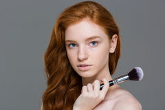 Portrait of beautiful tender young woman with big makeup brush Royalty Free Stock Photos