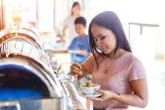 Portrait of beautiful thai asian women hand holding mush or boiled rice pork for thai style at buffet in restaurant, Breakfast buf royalty free stock images