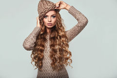 Portrait of beautiful thoughtful blond. Woman with long hair, brown sweater and hat Stock Photo