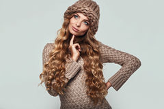 Portrait of beautiful thoughtful blond. Woman with long hair, brown sweater and hat Royalty Free Stock Images
