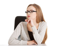 Portrait of beautiful thoughtful woman in eyeglasses sitting. Royalty Free Stock Image