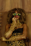 Portrait of a beautiful thoughtful young African woman wearing gold jewelry and sunglasses holding hand near face, bronze backgrou Royalty Free Stock Image
