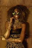 Portrait of a beautiful thoughtful young African woman wearing gold jewelry and sunglasses holding hand near face, bronze backgrou Stock Images