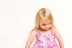 Portrait of Beautiful Toddler Girl Looking Dow. Closeup Portrait of Beautiful Toddler Girl Looking Down on Neutral Background Royalty Free Stock Photography