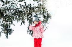 Portrait of a beautiful toddler girl playing outdoors with snow. Happy little child enjoying a winter day in the park or. In the forest Royalty Free Stock Image