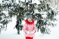 Portrait of a beautiful toddler girl playing outdoors with snow. Happy little child enjoying a winter day in the park or. In the forest Royalty Free Stock Photos