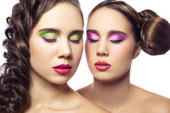 Portrait of beautiful twins young fashion women with hairstyle and red pink green makeup. isolated on white background. Royalty Free Stock Photos