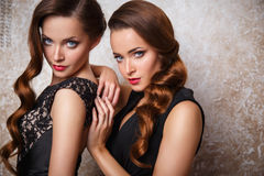Portrait of beautiful twins young women in gorgeous evening dresses Royalty Free Stock Images