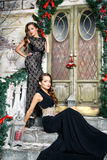 Portrait of beautiful twins young women in gorgeous evening dresses over christmas background Royalty Free Stock Photos