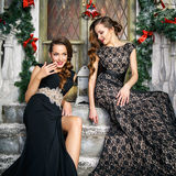 Portrait of beautiful twins young women in gorgeous evening dresses over christmas background Royalty Free Stock Images