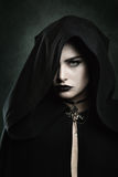 Portrait of a beautiful vampire woman. Dark portrait of a beautiful vampire woman with black hood . Halloween and horror concept Stock Image