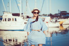 Portrait of beautiful white Caucasian brunette woman with tanned skin in blue dress, by seashore lakeshore. With blurry yachts boats on background on water Royalty Free Stock Photos