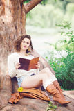 Portrait of beautiful white Caucasian girl woman with long dark red brown hair, in shorts and sweater, sitting in summer park Stock Photography